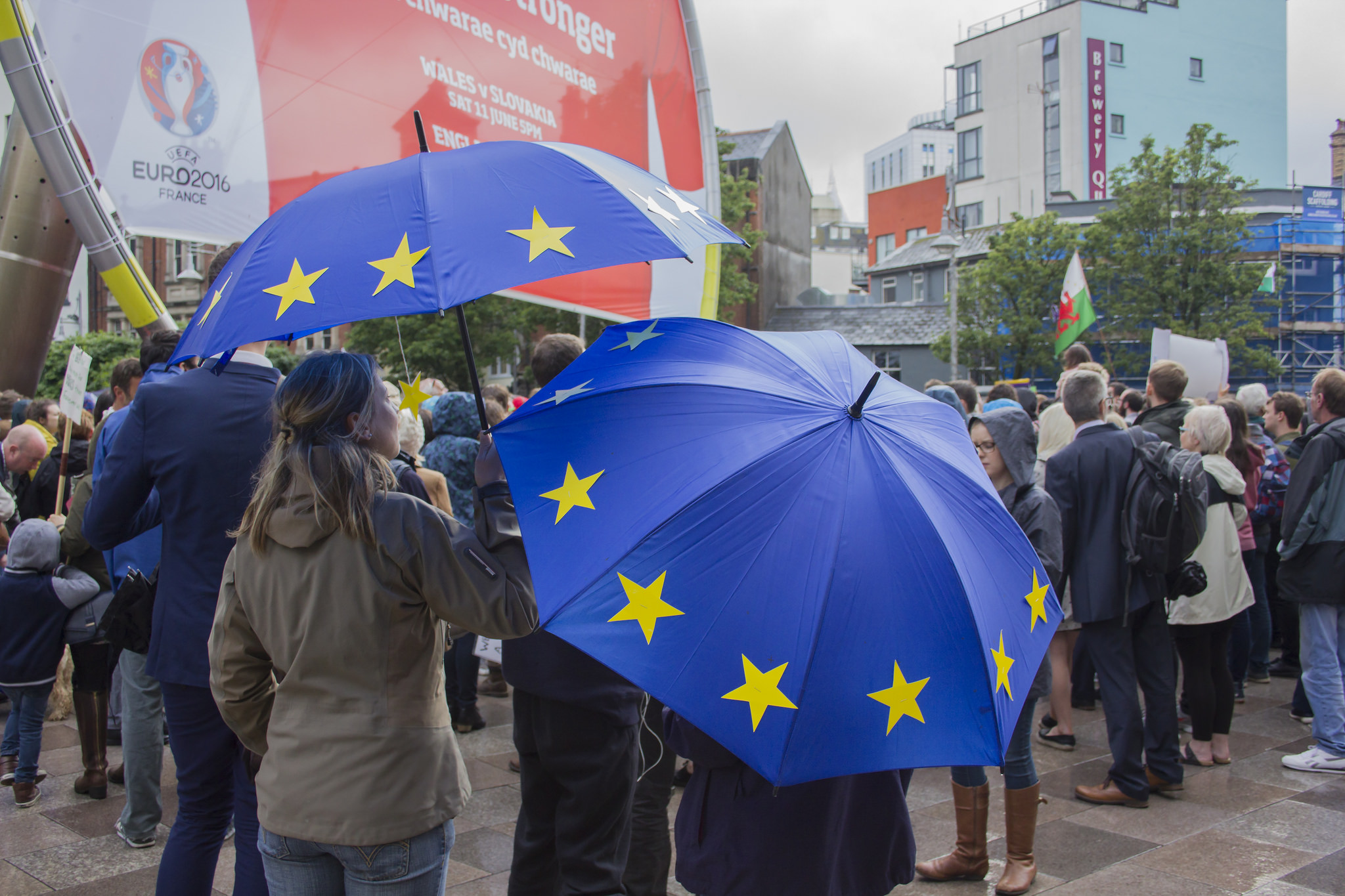 A pair of ladies holding two EU umbrellas in a crowd
